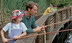 A father and daughter fish from a wooden bridge with cane fishing poles.